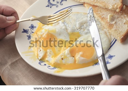 A man holds a fork and knife in preparation for eating his breakfast. - stock photo