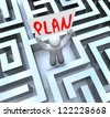 A man holds a sign with the word Plan in a maze or labyrinth to symbolize a way out - stock photo