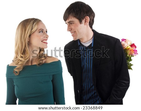 A man holds flowers behind his back and looks at his girlfriend