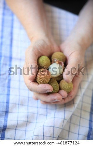 A man holds fresh lychee fruits, one peeled, in his hands.