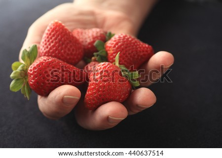 A man holds fresh, ripe strawberries in his hand on a black background. - stock photo