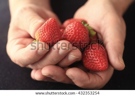A man holds fresh strawberries in both hands. - stock photo