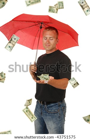 A man holds his hand out to catch falling money - stock photo