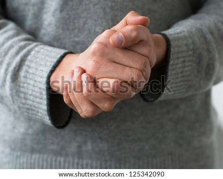 A man holds his hands folded - stock photo