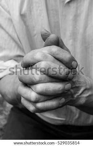 A man holds his hands in front of him. Fingers intertwined.