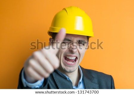 A man holds his helmet raised a thumbs up