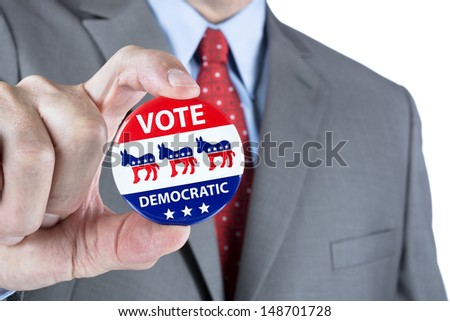 A man holds up a democratic vote badge lapel pin