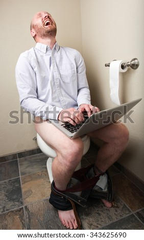 A man hysterically laughing while using his computer on the toilet - stock photo