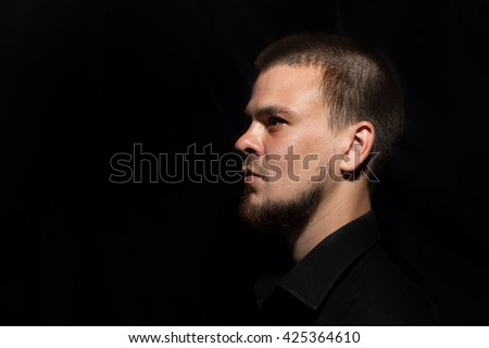 A man in a black shirt with the beard. Portrait of a man on a black background. Brutal. Portrait in low-key. A man looks into the distance. Sight. Opinion. Male view