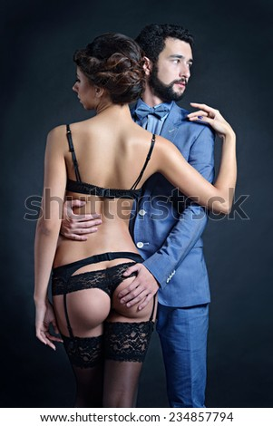 A man in a blue suit holding hands on the ass of a beautiful girl in black lingerie