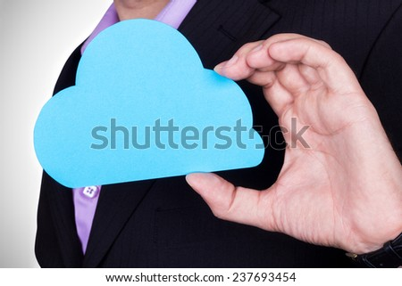 A man in a business suit holding a stencil clouds. The concept of cloud computing and remote data storage. The theme of IT and innovative solutions for business. Business solutions. - stock photo