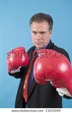 A man in a business suit with boxing gloves on, ready to punch the camera. - stock photo