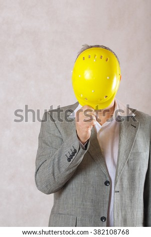 A man in a classical costume hides his face with a protective helmet.