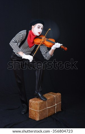 a man in a clown suit playing the violin
