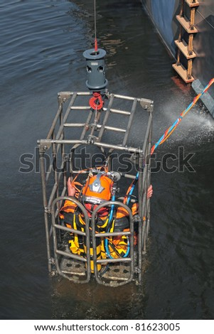 A man in a diving equipment, lift up out of the water in a special cage