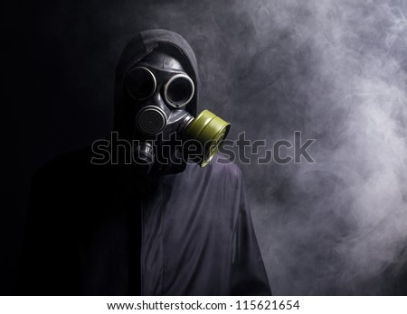 A man in a gas mask in the smoke. black background - stock photo