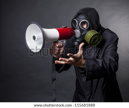 a man in a gas mask with a megaphone calling for help - stock photo