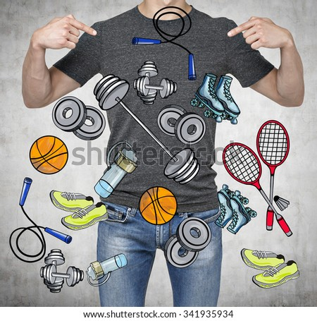 A man in a good physical form is pointing out the fingers on the colourful sport icons. Concrete background. a concept of a healthy lifestyle. - stock photo