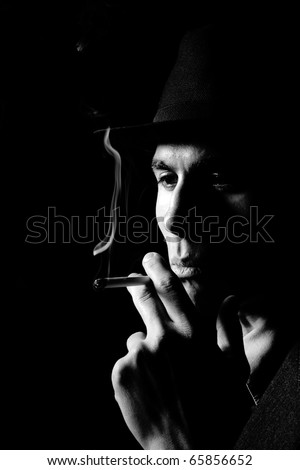 a man in a grey hat on black background smoking a cigarette - stock photo