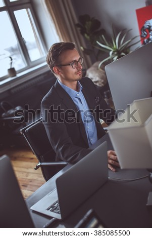 A man in a grey suit working on computer in the office.