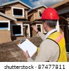 A man in a hard hat standing in front of an house holding a clipboard in his hand. - stock photo