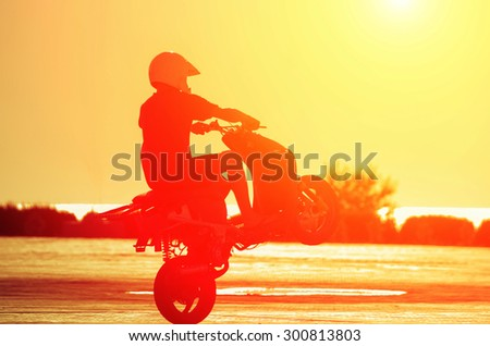 A man in a helmet on a moped shows stunts at sunset. Natural composition