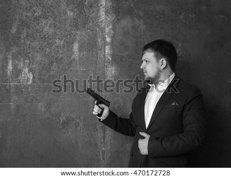 A man in a jacket and a pistol  Black and white. The concept of a serious man with a gun