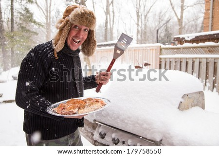 A man in a scarf and fur hat goes out in the snow to light his barbecue while the thermostat reads a chilling minus 10 degrees.  Good concept for being tired of winter and ready for a sunny vacation. - stock photo