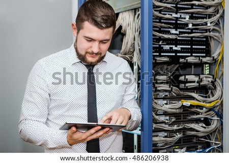 A man in a server room. A man in a shirt and tie, portrait. Internet service provider, data storage, system administrator, manager.