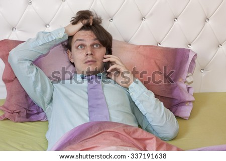 A man in a shirt and tie lying in bed, woken up by a call on some emergency situation, holding his hair - stock photo