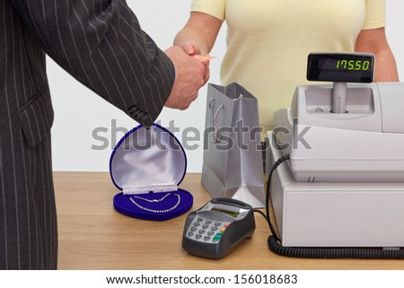 A man in a shop buying a necklace and handing the assistant his credit card to pay.