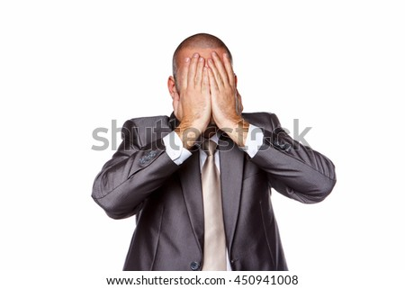 A man in a suit closes his face with arms. Isolated on a white background.