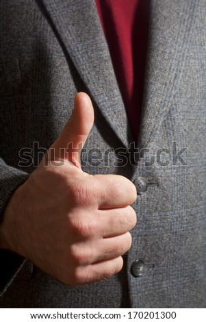 A man in a suit hand gesturing thumbs up - stock photo