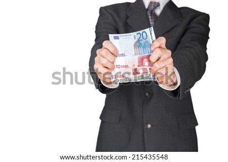 A man in a suit holding out a number of euro banknotes with two hands