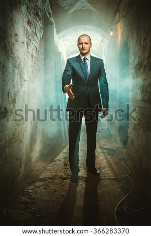 A man in a suit holds out his hand - stock photo