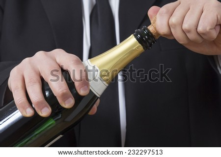 A man in a suit opening a bottle of Champagne
