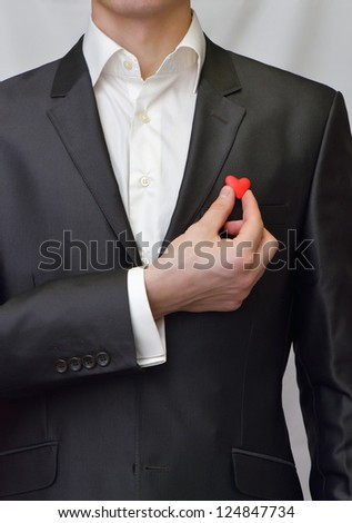 A man in a suit with a red heart in her hand - stock photo