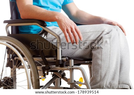 A man in a tracksuit sitting on a wheelchair - stock photo