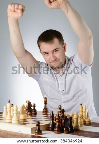 A man in a white shirt, clasped his hands in a fist on chess - stock photo