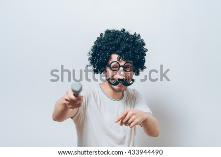 A man in a wig and funny glasses, singing into the microphone - stock photo