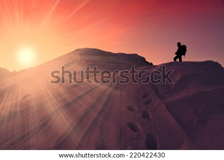 A man in beautiful  mountain sunset winter landscape  snow background