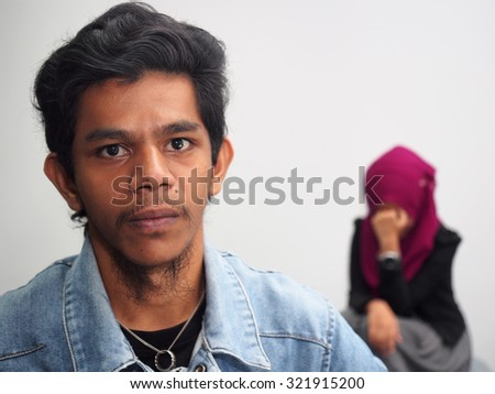 A man in foreground, after a fight with a woman (far). - stock photo