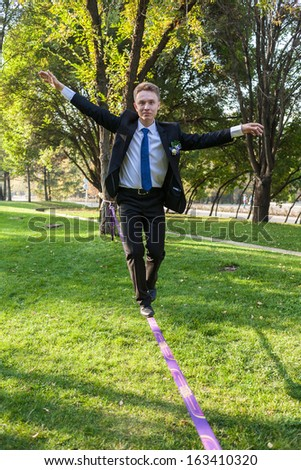 A man in formal suit is on a tightrope Slack-line - stock photo