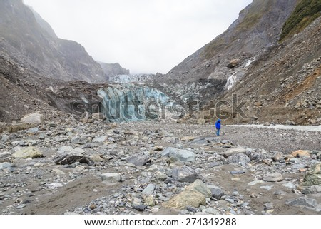 A man in front of the ice tongue of Fox glacier in New Zealand - stock photo