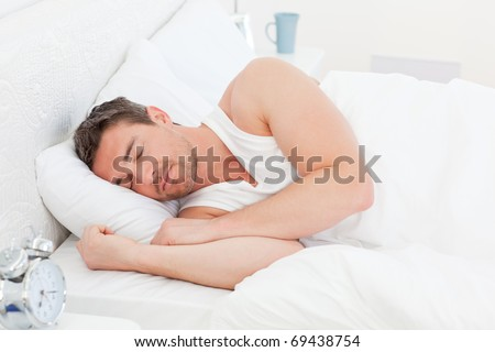 A man in his bed before waking up in his bedroom