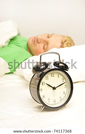 A man in his bed before waking up in his bedroom - stock photo