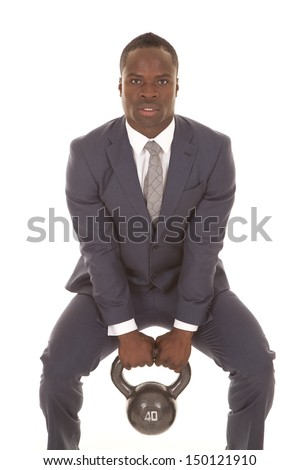 A man in his business suit working out his muscles with a kettle bell. - stock photo