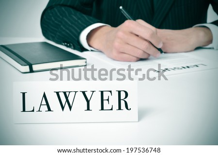 a man in his desk with a nameplate in front of him with the word lawyer written in it - stock photo