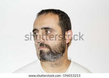 A man in his forties with half face shaved, half face unshaven (beard), doubting about what to do