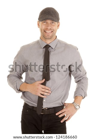 A man in his gray shirt and tie smiling while wearing a hat. - stock photo